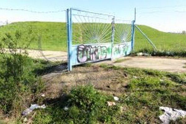 Diera v plote je hneď vedľa hlavnej brány. Prejde ňou aj dospelý.