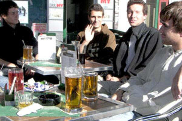 Partia ôsmich mládencov si vychutnáva jedno z posledných posedení na letnej terase.