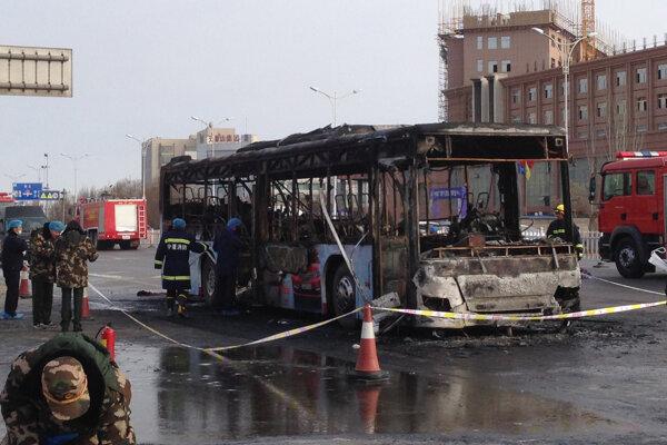 Hasiči pracujú na mieste zhoreného autobusu v čínskom meste Jin-čchuan.