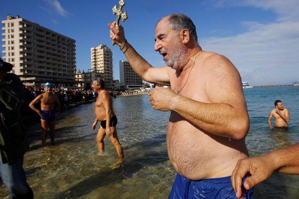Plavec vychádza na pevninu s krížom, ktorý hodili do mora v súvislosti s obradom svätenia.
