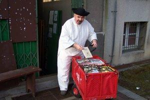 Jano Cíger počas balenia kníh do vozíka pred antikvariátom.