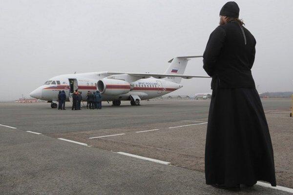 Pravoslávny kňaz čaká na ruský vládny špeciál, ktorý priviezol pozostatky obetí zo Sinaja.