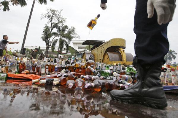 Pracovník indonézskych úradov ničí zhabaný ilegálny alkohol.