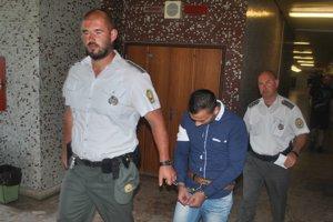 Milan s eskortou. Odvádza ho späť do väznice.