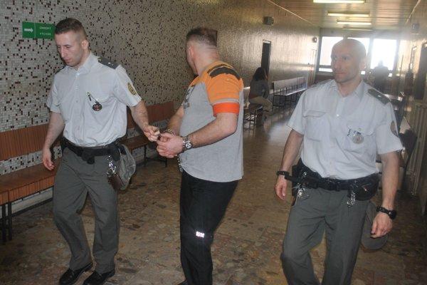 Marcel s eskortou. Vedú ho späť do väzby.