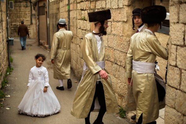 Ultraortodoxní židia kráčajú okolo dievčatka vkostýme počas osláv sviatku Purim vJeruzaleme. (AP Photo/Sebastian Scheiner)