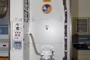 Záchod, ktorý je na ISS od roku 2008. Hadica so žltým koncom slúži na odsávanie moču. Strieborná nádoba slúži na stolicu.