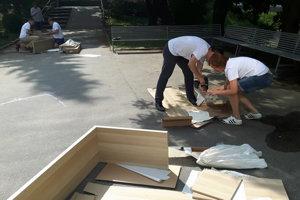 Riaditelia firiem pomáhajú na Základnej škole Dubová. Časť skladá nábytok, ďalší maľujú plot.
