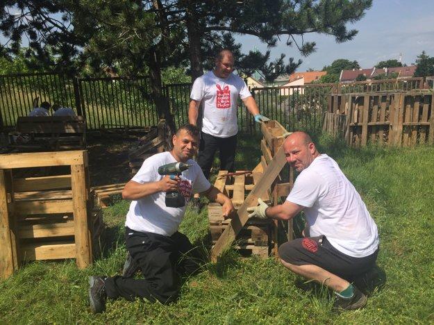 Dobrovoľníci skúšajú nosnosť lavičky, ktorú zložili z paliet pre žiakov Spojenej školy Mudroňovej v Nitre.