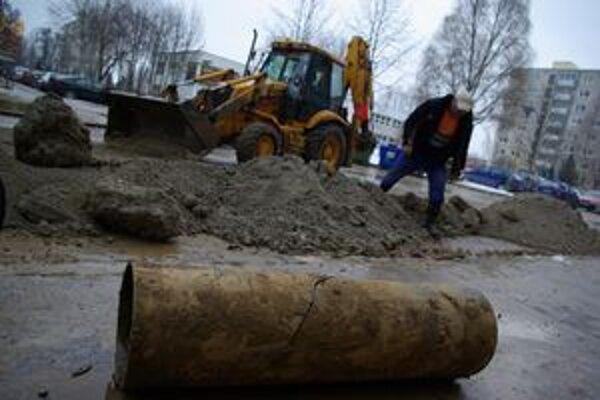 Príčina havárie - prasknutý kus vodovodného potrubia. Za ňou buldozér a pracovník SEVAK-u, ktorí po 15. hod zasýpali už opravené potrubie.