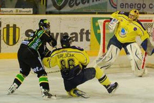 Útočník Žiliny Róbert Krajčí tiesnený obrancom Kežmarku Danielom Brejčákom dokázal vystreliť puk na brankára hostí Martina Klempu, ktorý ho stihol vyraziť.