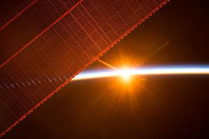 Jeden zo šestnástich východov Slnka, ktoré astronauti na ISS videli 26. júla 2017. Solárne panely produkujú viac energie, než stanica potrebuje, a tak nabíjajú zároveň batérie, ktoré ISS poháňajú v tme.