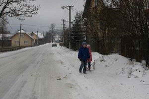 Sneh z chodníkov obec nemá ako odvážať. Pluh ho zhŕňa k plotom rodinných domov.