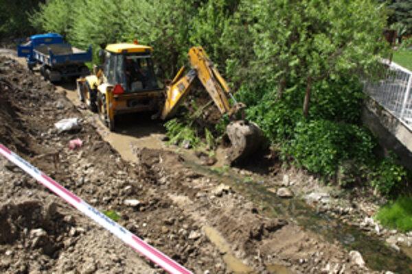 Na jednej strane robotníci upravujú svah pod parkovisko, na druhej čistia koryto potoka. Brehy treba spevniť, aby ich nepodmývala voda.