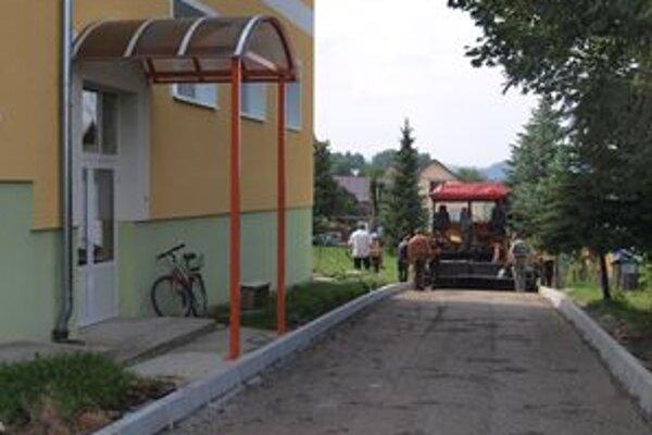 Robotníci naťahujú na rozbitú príjazdovú cestu kMŠ vo Vavrečke nový asfaltový koberec.