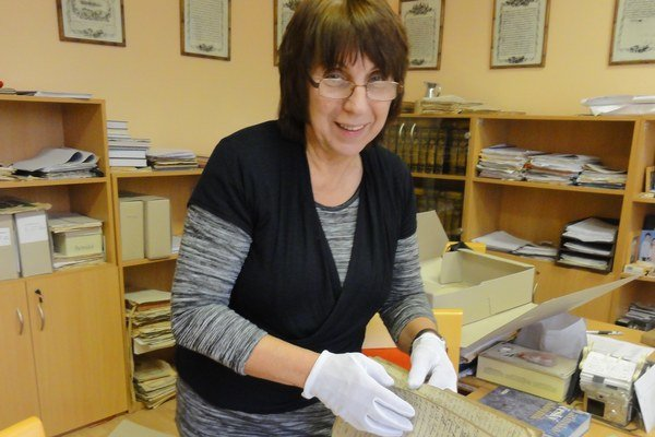 Riaditeľka topoľčianskeho archívu Oľga Kvasnicová listuje v objavených knihách.