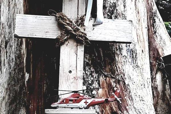 Jednoduchý kríž s modelom záchranárskeho vrtuľníka na mieste tragédie.