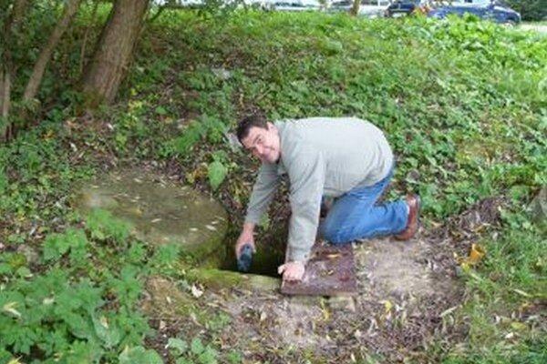 Peter Bojnický ukazuje, ako sa voda zo studničky zle naberá.