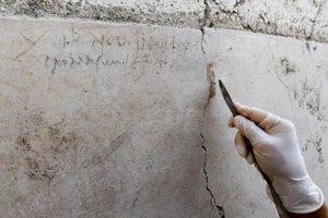 Archeologička kontroluje nápis na stene počas archeologických prác v antickom talianskom meste Pompeje