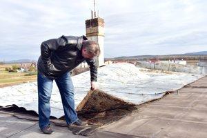 Starosta obce Andrej Kulik kontroluje škody na poškodenej streche po veternej smršti na obecnom úrade.