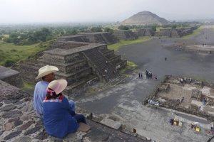 Turisti sediaci na Pyramíde Mesiaca. V pozadí Pyramída Slnka.