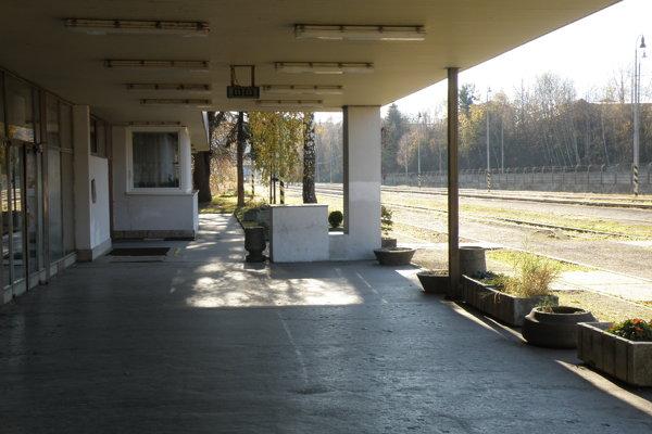 Ľudia pri čakaní na vlak postávajú alebo sedia na betónových kvetináčoch.