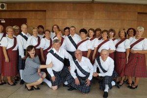 V škótskych sukniach. Seniori optimisti a ich trénerka Stella Víťazková.