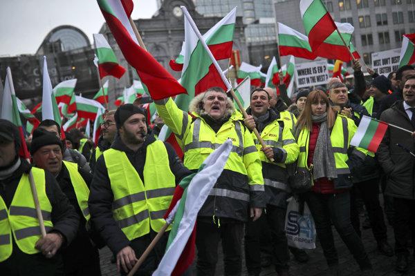 Demonštranti v Bruseli mávajú bulharskými vlajkami.