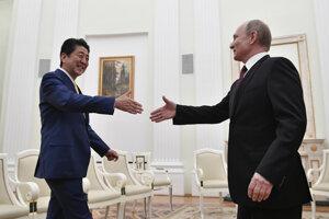 Japonského premiéra Šinzóa Abeho víta v Moskve Vladimir Puin.