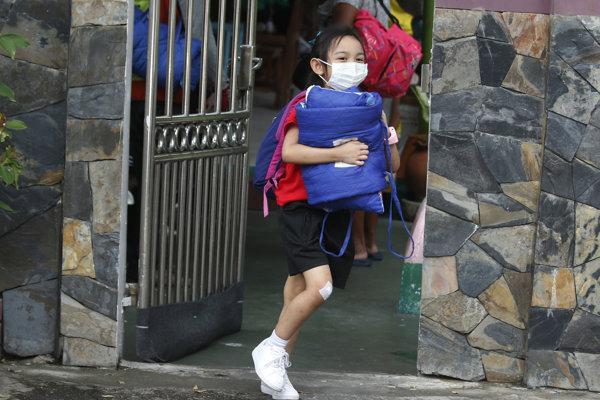 Žiak s ochranným rúškom na tvári uteká zo školy počas hustého smogu v Bangkoku.