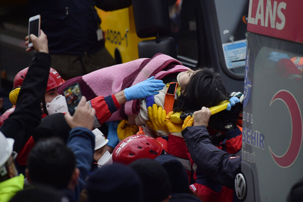 Záchranári prevážajú päťročné dievča na nosidlách do sanitky.