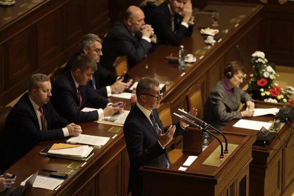 Na snímke dole český premiér Andrej Babiš reční na pôde českého parlamentu v Prahe.