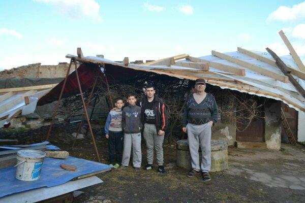 Jozef Varga s vnukmi Tiborkom, Sebastiánkom a Dávidkom pred zničeným domom.