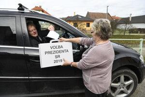 Imobilný volič vhadzuje obálku s hlasovacím lístkom do mobilnej volebnej schránky z auta pred volebnou miestnosťou v obci Drietoma.