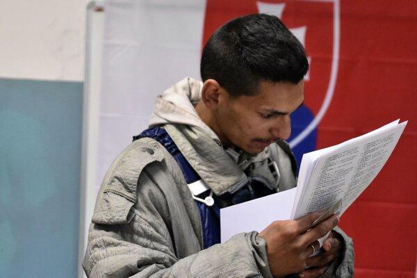 Volič z Trebišova číta hlasovací lístok vo volebnej miestnosti. Rómska strana sa v parlamentných voľbách 2016 nenachádzala, jednotliví rómski kandidáti boli málo viditeľní.
