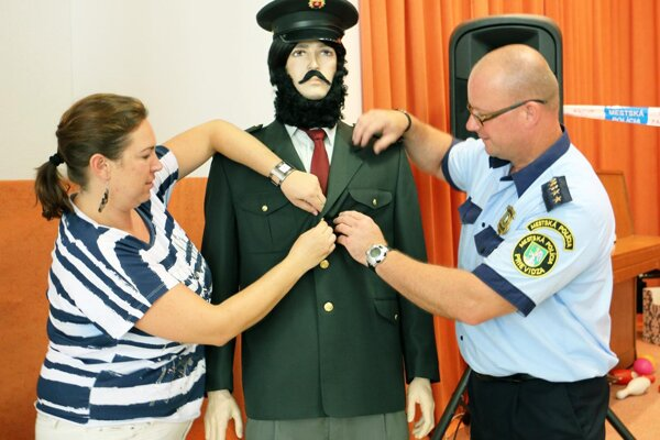 Manažérka kultúry RKC Monika Bartušová (vľavo) a hovorca mestskej polície Vít Zajac obliekajú figurínu Ľudovíta Štúra do policajnej uniformy.
