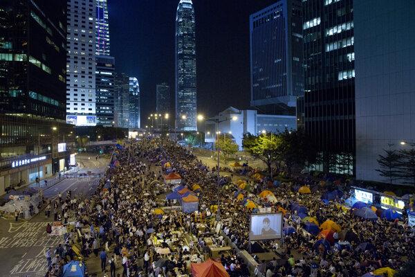 Prodemokratickí demonštranti sledujú na veľkoplošnej televíznej obrazovke rozhovory medzi hongkongskými vládnymi predstaviteľmi a študentmi počas protestného zhromaždenia pri vládnom sídle v miestnej štvrti Admiralty v Hongkongu 21. októbra 2014.