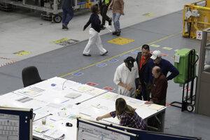 Pracovníci sa zhromažďujú pri stole na výrobnej linke pre Boeing 737 MAX 8 počas krátkej prehliadke pre médiá v montážnom závode v americkom meste Renton. (27. marca 2019)