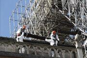 Robotníci na streche katedrály Notre Dame odstraňujú zhorenú časť krovu.