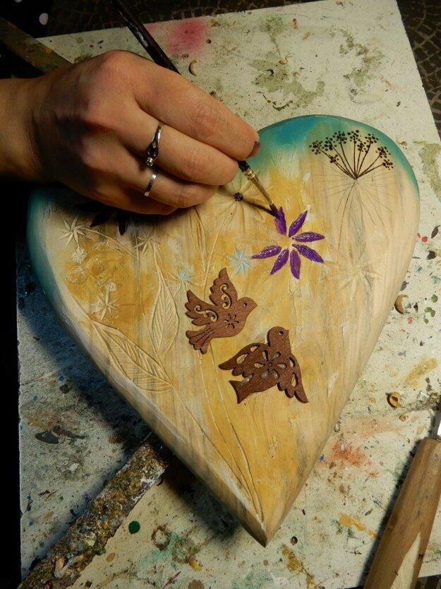 Umelkyňa maľuje na srdiečka rôzne motívy.