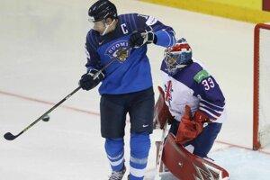 Fínsky kapitán Marko Antilla tečuje puk pred britkým brankárom Benom Bownsom v zápase Fínsko - Veľká Británia na MS 2019 v hokeji.
