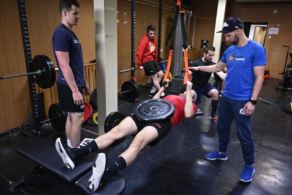 Hokejisti Dukly Trenčín trénujú počas letnej prípravy v posilňovni pod dohľadom kondičného trénera Stanislava Magulu (na snímke vpravo).