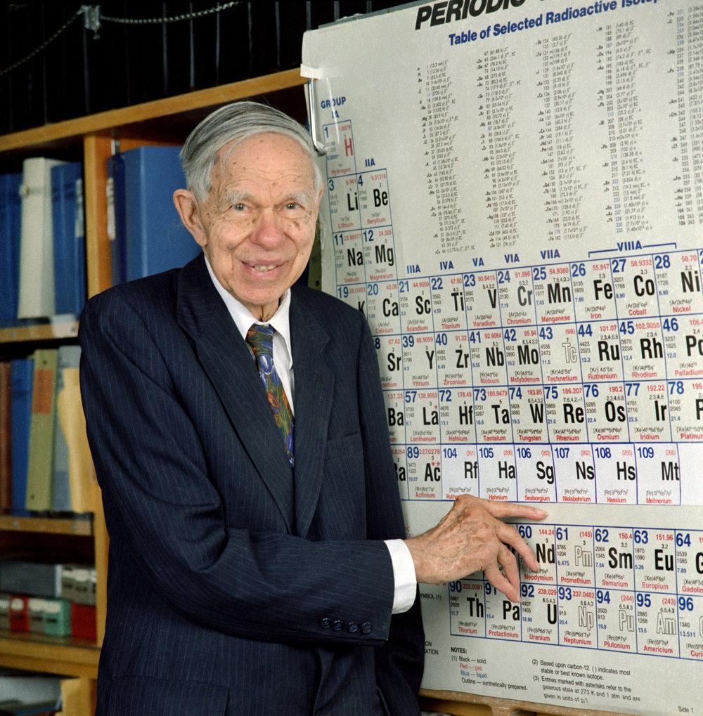 Chemik Glenn Seaborg pri periodickej tabuľke. Ukazuje na prvok seaborgium, ktorý nesie jeho meno.