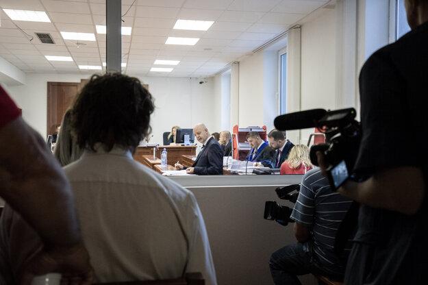 Novinári sledujú súdne pojednávanie.