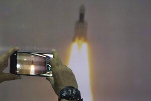Muž si robí záber zo živého vysielania na webe v planetáriu v Naí Dillí.