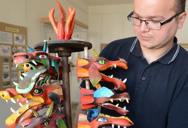 paleontológ Peter Ledvák ukazuje výtvarné spracovanie dračích hláv.