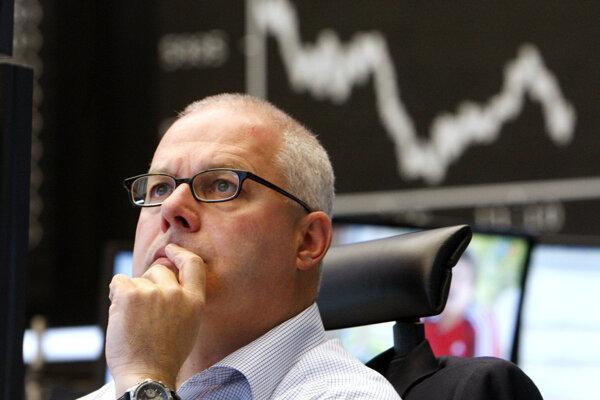 Maklér sleduje monitory na burze cenných papierov v nemeckom  Frankfurte.