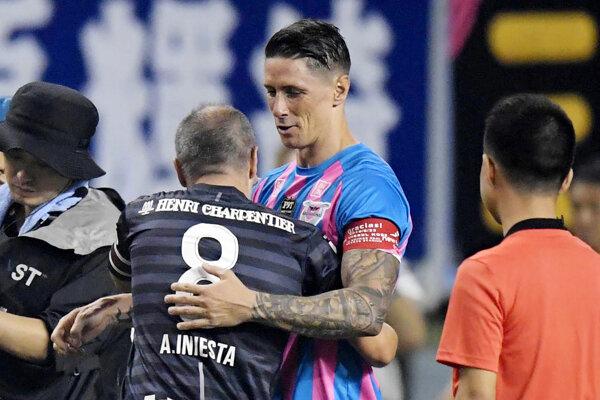 Fernando Torres v objatí Andresa Iniestu.