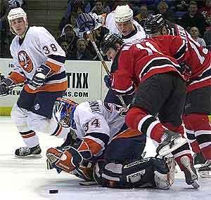 john madden z new jersey devils padá na brankára new yorku islanders johna vanbiesbroucka, ktorý sa snaží chytiť puk v zápase hokejovej nhl v uniondale, 31.1.2001. celú akciu sleduje dave scatchard (38) z n.y. lslanders. tasr