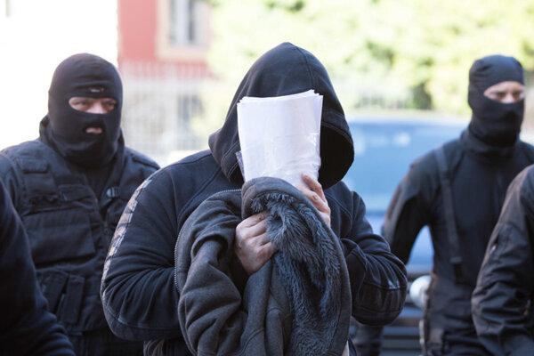 Takto 13 obvinených vlani v októbri predvádzali pred sudcu, ktorý ich vzal do väzby. Dnes je za mrežami už len jeden z nich.